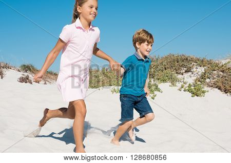 Two kids holding hands running away on sandy beach. Happy smiling little girl and cute boy running down the dunes at the beach. Joyful kids running barefoot at the beach.