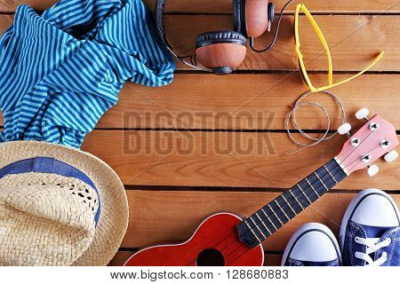 Small guitar, headphones and clothes on wooden surface, top view