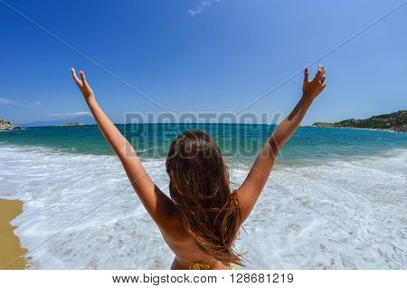 Young girl with her hands up saying hello to the beautiful sandy beach with white foamy waves in a sunny windy day Greece Sithonia