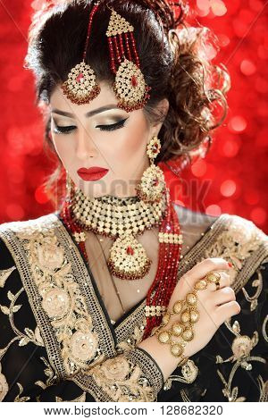 Portrait of a beautiful female model in tradition asian indian bridal costume with heavy jewellery and makeup poster