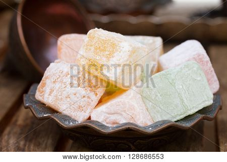 Lumps of Lokum or Turkish Delight in a tradition vase on wooden table  close up