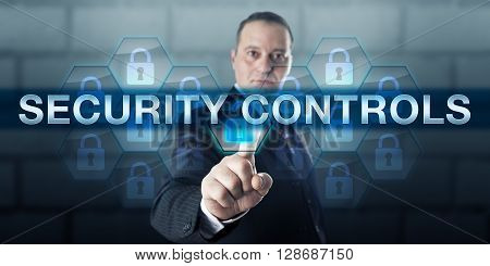 Information manager is pressing SECURITY CONTROLS on an interactive touch screen interface. Business risk metaphor and information technology concept for protection of integrity of data.