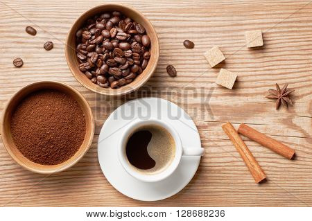 Coffee beans, ground coffee and cup of brewed coffee on rustic wooden table decorated cinnamon sticks, star anise, cane sugar and coffee beans, view from above