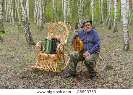 Senior man is having rest in birch forest sitting on a wicker stool and holding mandolin