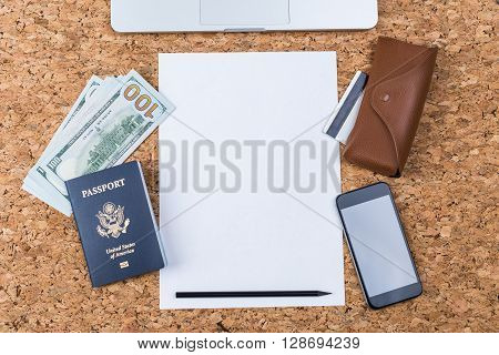 Top view of cork table with blank paper sheet smartphone eyeglass case american passport and dollars. Traveling concept. Mock up