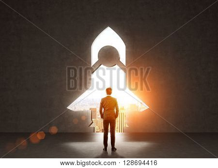 Start up concept with businessman standing in front of rocket shaped gap in wall revealing sunlit New York city view