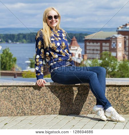 Portrait in full growth, Young beautiful woman in blue jeans sitting in summer street park