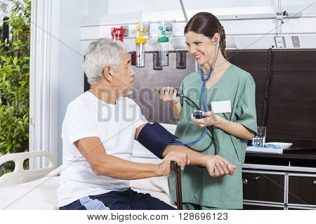 Nurse Checking Blood Pressure Of Senior Man In Rehabilitation Ce