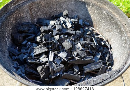 Charcoal briquettes firing up for the grill in the evening sun