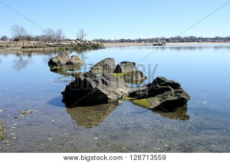 Large jagged rocks at the edge of a channel exposed to boaters, at the edge of a channel.