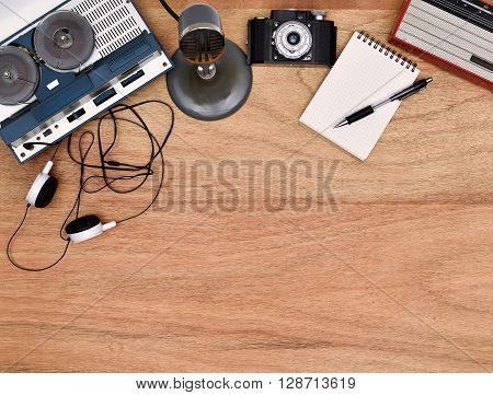 Old retro reel tape recorder vintage radio retro camera on wooden table. Blank notepad and pen.