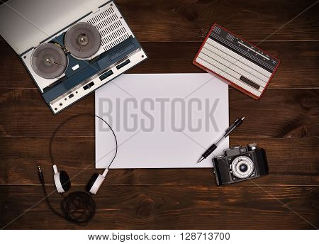 Reel tape recorder with headphones vintage radio retro camera on wooden table. Plank paper. View from above