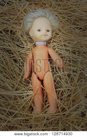 old abandoned doll lays on the hay
