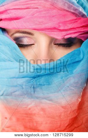 Young woman makeup on eyes hiden her face with multicolored shawl blue background