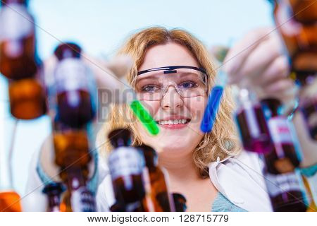 Experiment research in progress. Chemist woman or student girl laboratory assistant or scientific researcher with chemical glassware test flask on blue