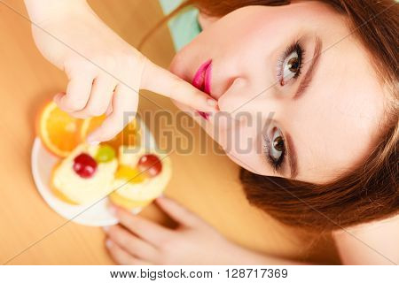 Woman eating delicious gourmet sweet cream cake cupcake and orange showing hand quiet sign gesture. Glutton girl having breakfast in secrecy. Appetite and gluttony concept. poster