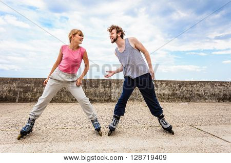 Two People Exercise Stretch Outdoor On Rollerblades.