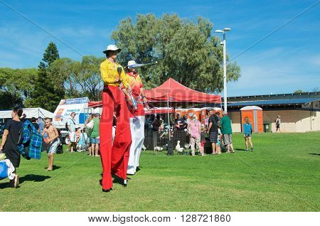 COOGEE,WA,AUSTRALIA-APRIL 3,2016: Lifeguard stilt walkers and families at the Coogee Beach Festival in Coogee, Western Australia.