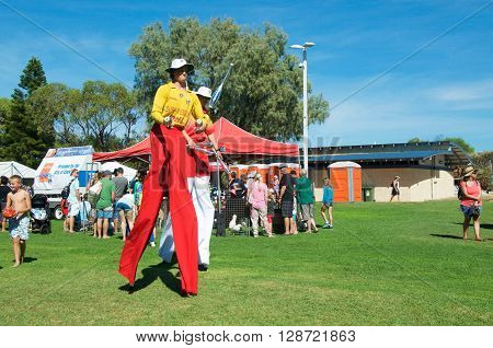 COOGEE,WA,AUSTRALIA-APRIL 3,2016: Juggling lifeguard stilt walkers and people at the Coogee Beach Festival in Coogee, Western Australia.