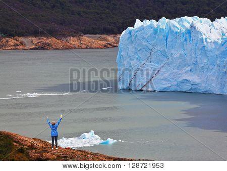 Giant lake Perito Moreno glacier. The woman - tourist admire the white-blue icy splendor