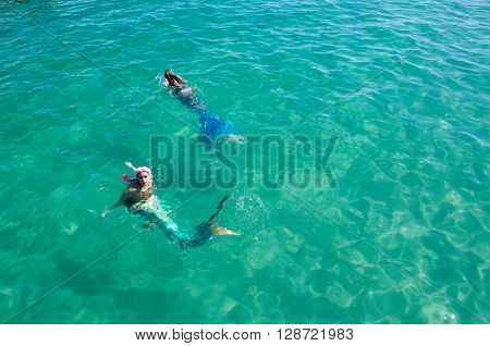 COOGEE,WA,AUSTRALIA-APRIL 3,2016: Two live interactive mermaid entertainers swimming in the turquoise Indian Ocean waters at the Coogee Beach Festival in Coogee, Western Australia.