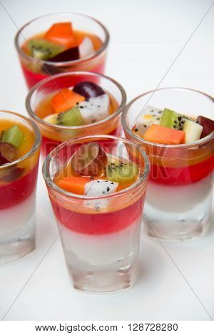 Fruit jelly in the glass toped with fresh fruit.