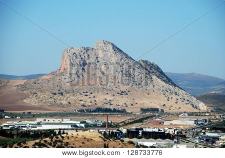 ANTEQUERA, SPAIN - JULY 1, 2008 - View of the Lovers rock (Pena de los Enamorados) with industrial units in the foreground Antequera Malaga Province Andalucia Spain Western Europe, July 1, 2008.