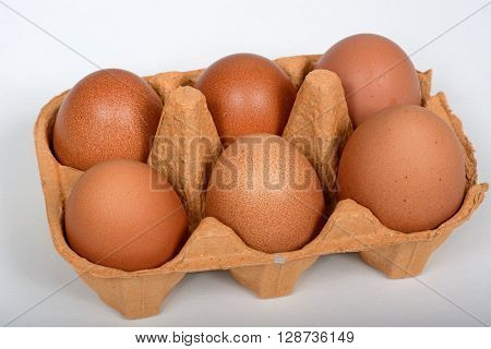 Six fresh brown eggs in a brown cardboard box against a white background.