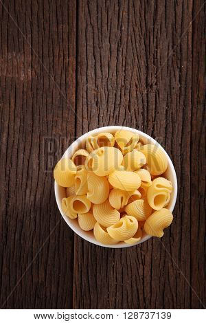 bowl of pipe rigate pasta on the wooden background