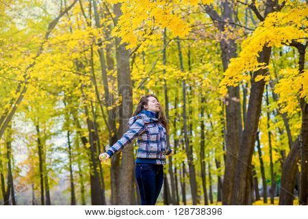 girl in autumn park spinning merrily among the yellow leaves