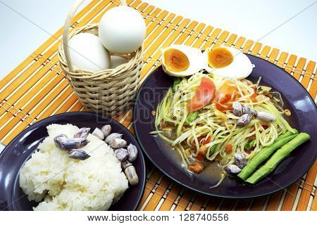 Thai Som Tum / Papaya Salad / Papaya Pok Pok with sticky rice on orange bamboo mat. Focus on Papaya Salad.