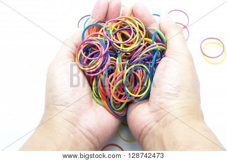 Colorful rubber/elastic bands in hand, isolated on white.