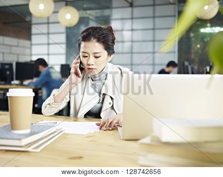 young asian office worker sitting at desk calling using mobile phone in office.