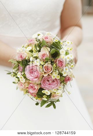a bride with bouquet of pink roses no face