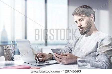 Businessman using laptop and mobile phone at his desk in office with New York city view