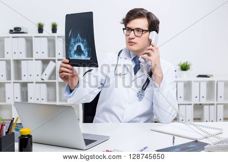 Young doctor at office desk examining an x-ray and talking on the phone