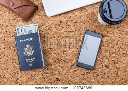 Top view of cork desktop with dollar banknotes inside american passport blank phone coffee cup and eyeglass case. Traveling concept. Mock up
