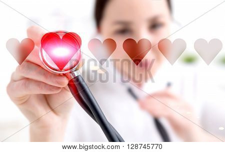 Female doctor listening to abstract heartbeat with stethoscope
