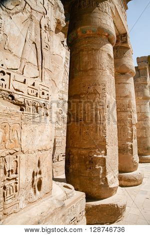 Egyptian paintings carving figures and hieroglyphs in columns and wall of landmark Temple of Ramses or Ramesses III at Medinet Habu monument in Luxor Egypt Africa