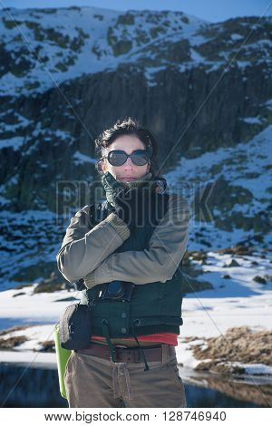 portrait of sport active woman with green vest brown trousers standing in snow looking hands gloves in face with camera in Gredos mountain Avila Spain Europe
