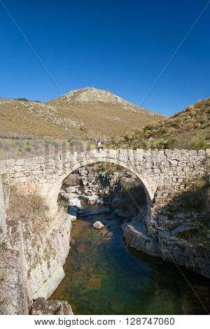 woman with white shirt greeting arm up from ancient Roman stone bridge over Barbellido River in Pozo Paredes Navacepeda de Tormes Gredos mountain Avila Spain Europe
