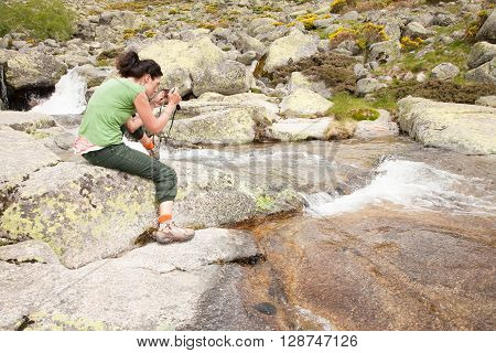 brunette tourist woman with green shirt and trousers sitting on rock with camera photo as photographer taking picture of water river in Gredos mountain Avila Spain Europe