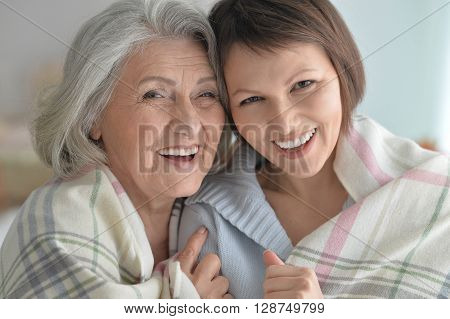 cheerful senior mother and adult daughter together