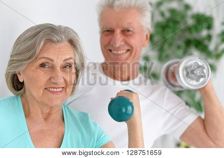 Happy sporty senior couple exercising with dumbbells