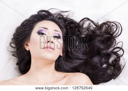 Front view of model portrait with black hair over white looking at you