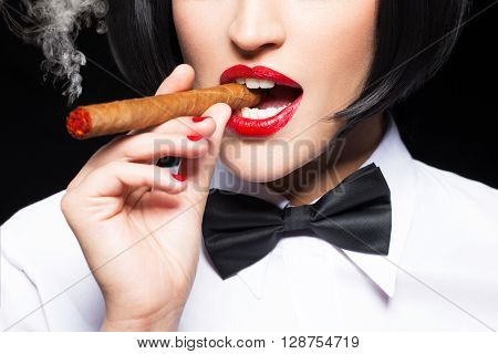 Sexy mafiosi woman smoke with cigar closeup isolated on black