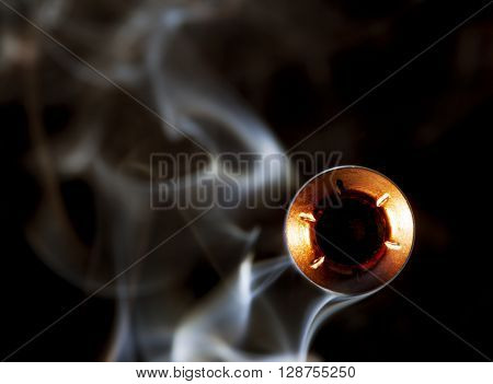 Hollow point bullet that is coming at the viewer with smoke