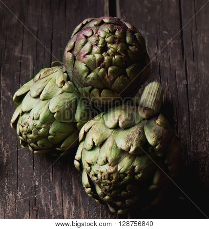 Ripe Organic Artichokes on the rustic wooden board  with lemon, napkin and knife