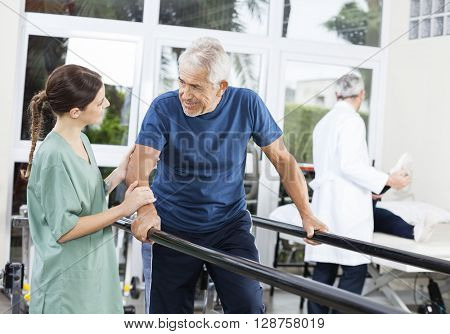 Patient Looking At Female Physiotherapist While Walking Between