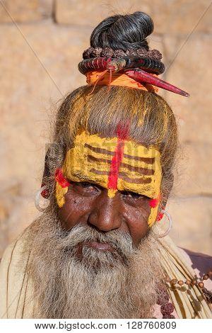 Hindu sadhu holy man sits on the ghat seeks alms on the street in Jaisalmer Rajasthan India . Close up